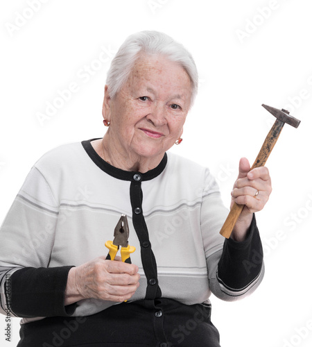 Old woman holding hammer and pliers