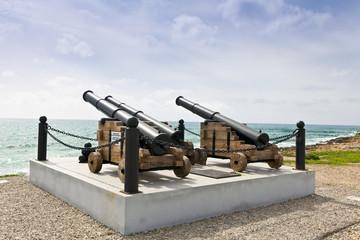 Historic guns at the harbor in Paphos facing the sea.