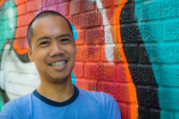 Asian male standing against graffiti wall, smiling