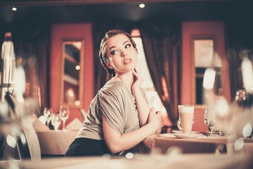 Beautiful young woman with cup of coffee alone in a restaurant