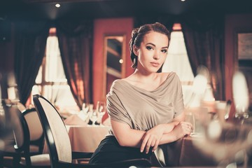 Beautiful young woman alone in a luxury restaurant interior