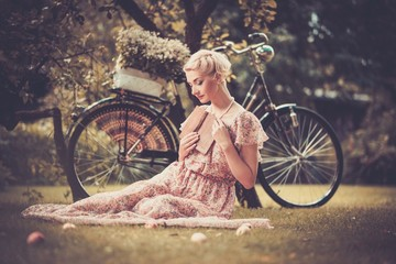 Dreaming blond retro woman sitting on a meadow