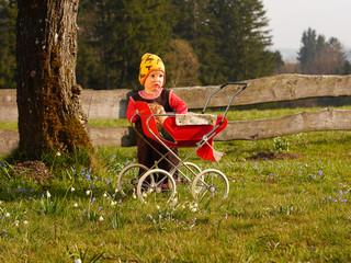 Kind mit Puppenwagen