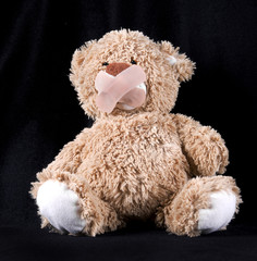 teddy bear with plaster on mouth