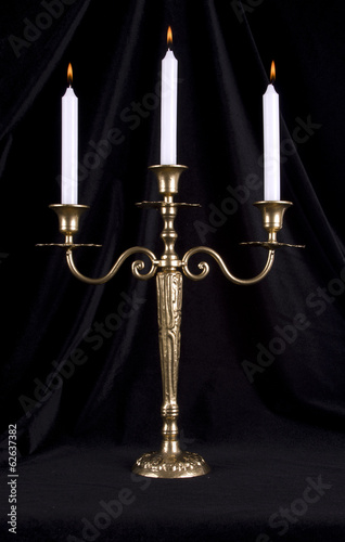 Vintage brass candelabrum with three burning candles