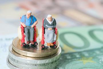 Altes Ehepaar im Rollstuhl mit Geld