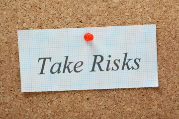 The phrase Take Risks on a cork notice board