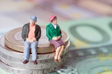 Oma und Opa auf einem Geldstapel