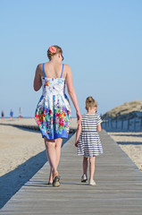 Little girl with mom on beach vacation.