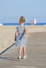 Little girl on beach vacation. From the back.