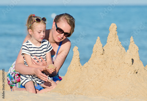 Family with sand castle on the beach.