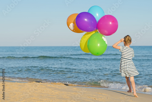 Little girl running with colorful balloons.