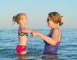 Woman teaching child to swim in the sea.
