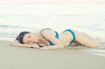 Woman lying on the beach sand.