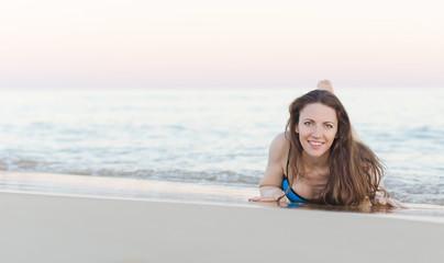 Woman lying on the beach sand.