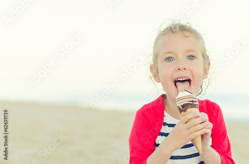 Little girl eating ice-cream on the beach.