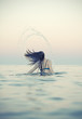 Woman in water waving hair. Vintage effect.