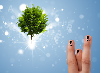 Happy finger smileys with green magical glowing tree