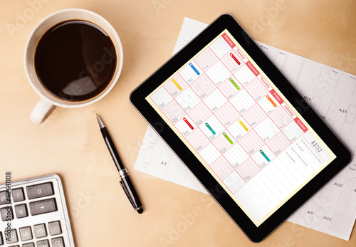 Foto op Plexiglas Koffie Tablet pc showing calendar on screen with a cup of coffee on a d