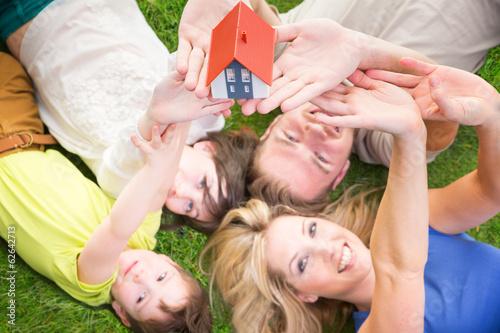 Familie liegt auf der wiese mit haus in der hand