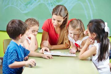 Erzieher beim Vorlesen von Buch im Kindergarten