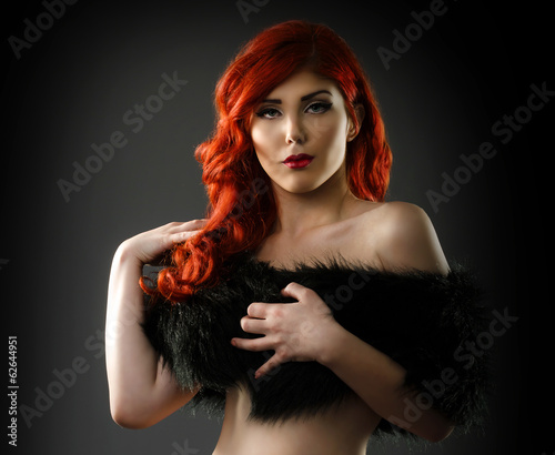 Sexy woman covering her breasts with a black fur coat