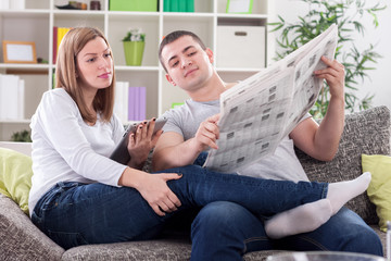 Woman with tablet and husband with newspaper reading news