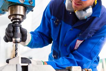 Handwerker bohrt mit Bohrmaschine in Fabrik