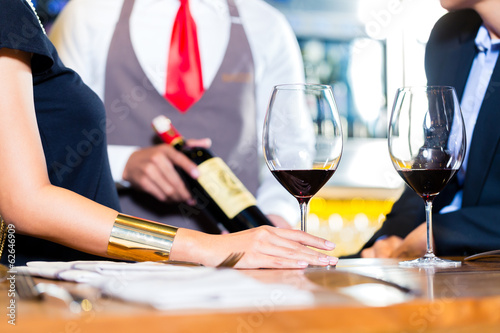Asian couple tasting red wine in bar