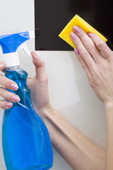 Woman washes a tile with clearing means