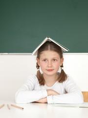 Schülerin hält ihr Buch auf dem Kopf