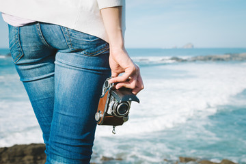 Female photographer holding vintage camera on travel