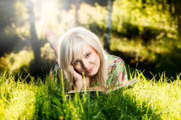 Young girl lies on green grass and reads book