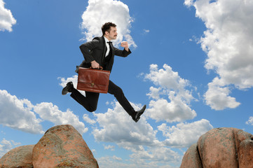 Businessman Jumping from Rock
