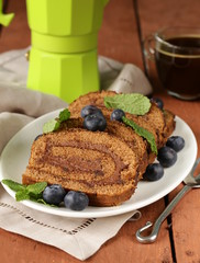 chocolate biscuit roll with mint leaves and blueberries