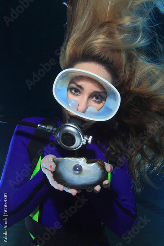 Female scuba diver with shell and pearl