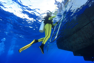 Scuba diver climb the ladder of the dive boat