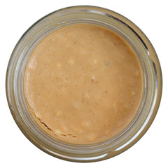 Glass jar of crunchy peanut butter shot from above.