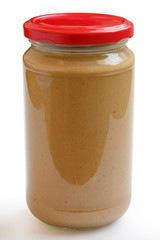 Closed glass jar of crunchy peanut butter with white background.