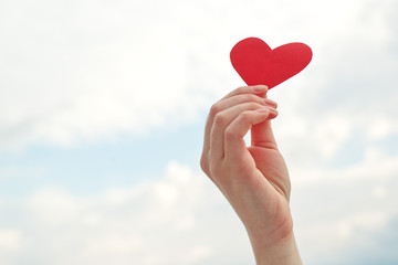 Female hand holding red paper heart