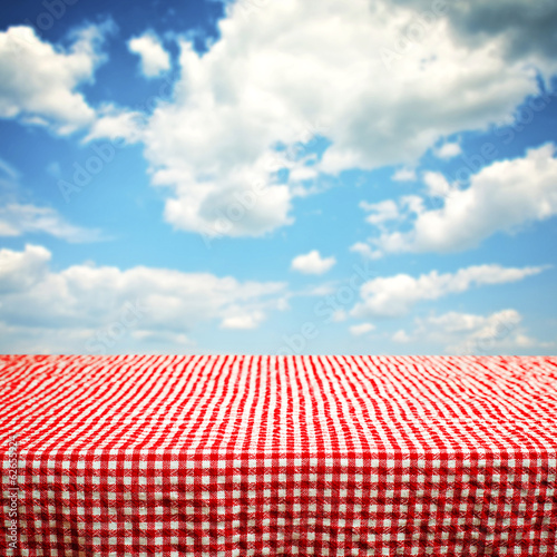 Empty wooden deck table with clouds in background