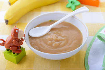 Puree from banana in child`s plate