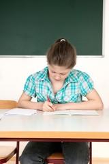 Schülerin sitzt im Klassenzimmer an einem Tisch und schreibt