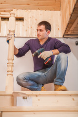 a young worker sitting and holding cordless drill