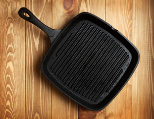 Frying pan on wooden table background