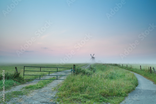 misty summer morning on Dutch countryside with windmill