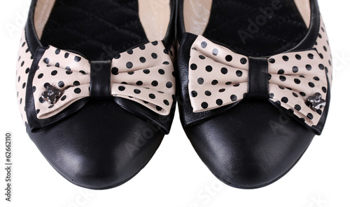 Female flat ballet shoes patterned with black polka dots