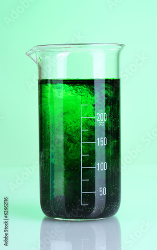 brightly ink in a flask with water on green background