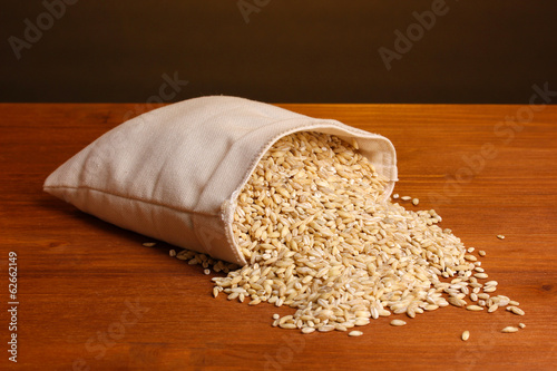 Cloth bag of wheat on wooden table on brown background