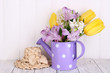 Flowers in watering can on table on wooden background